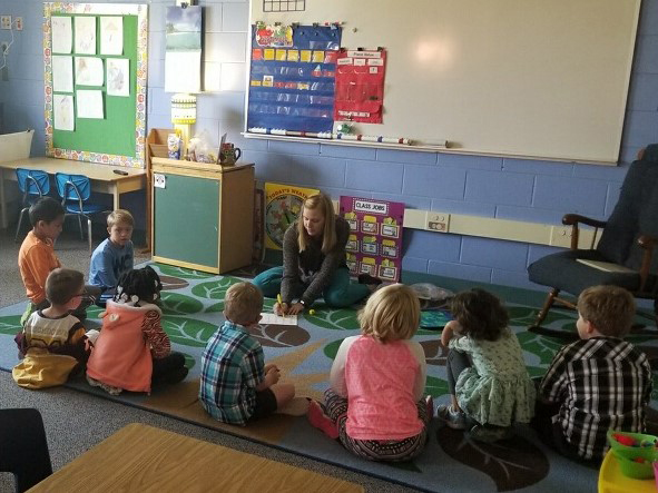 A teacher reads to students in a classroom